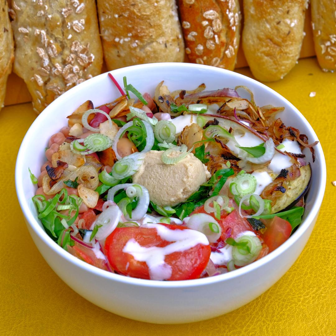 Bowl mit Hummus, Salat und Dressing, wahlweise mit gegrillten Aubergine und würzigem Tomatensalat.